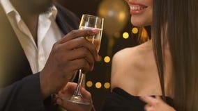 Vidrio proponente masculino negro de champán a la señora sonriente atractiva, recogida almacen de video