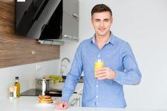 Vidrio que se sostiene masculino atractivo de jugo en la cocina Fotografía de archivo libre de regalías