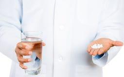 Vidrio que se sostiene profesional de la atención sanitaria de agua en una mano y las píldoras blancas Imagen de archivo libre de regalías