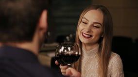 Vidrio romántico de la bebida de la fecha de los pares felices jovenes de vino rojo en el restaurante almacen de metraje de vídeo