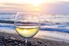 Vidrio romántico de vino que se sienta en la playa en los vidrios coloridos de la puesta del sol del vino blanco contra puesta de Fotografía de archivo libre de regalías
