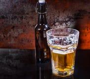 Vidrio semilleno de la cerveza y de la botella de cerveza en un surfac negro del espejo Imágenes de archivo libres de regalías