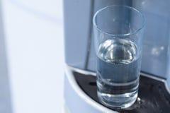 Vidrio semilleno en dispensador del agua Imagen de archivo