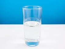 Vidrio semivacío o semilleno de agua en la tabla blanca (Para el pensamiento del positivo) Fotografía de archivo