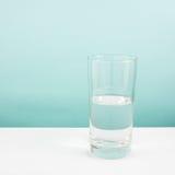 Vidrio semivacío o semilleno de agua en la tabla blanca (Para el pensamiento del positivo) Imágenes de archivo libres de regalías
