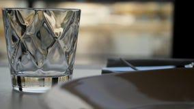Vidrio tallado de agua en fondo de la naturaleza Despeje el vidrio tallado con el whisky en una tabla de madera oscura, primer va fotos de archivo