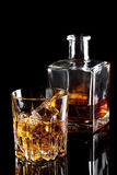 Vidrio tallado de whisky con hielo y una botella Imagen de archivo libre de regalías