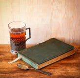 Vidrio-tenedor del té del vintage con los limones frescos y el libro viejo sobre la tabla de madera imagen filtrada retra foto de archivo libre de regalías