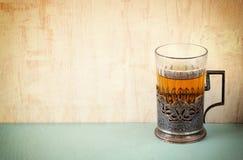 Vidrio-tenedor del té del vintage sobre la tabla de madera imagen filtrada retra foto de archivo