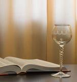Vidrio vacío y libro abierto Imagen de archivo