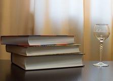 Vidrio vacío y libros cerrados Imagen de archivo libre de regalías