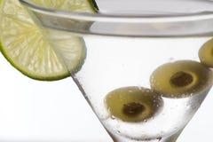 Vidrio y alcohol de Martini con las aceitunas verdes Imagen de archivo libre de regalías