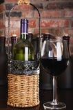 Vidrio y algunas botellas de vino rojo Imagen de archivo