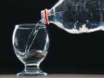 Vidrio y botella de agua de agua con el relleno del agua fotografía de archivo