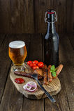 Vidrio y botella de cerveza con las salchichas, los tomates de cereza y la cebolla foto de archivo libre de regalías