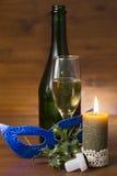 Vidrio y botella de Champán con la vela ardiente en viejo fondo de madera Foto de archivo libre de regalías
