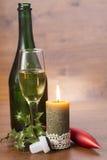 Vidrio y botella de Champán con la vela ardiente en viejo fondo de madera Imágenes de archivo libres de regalías