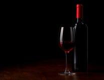Vidrio y botella de vino en un vector de madera Imagen de archivo