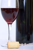 Vidrio y botella de vino rojo con el corcho y el sacacorchos Imagen de archivo libre de regalías
