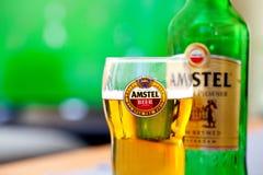 Vidrio y botella - fondo de Amstel de la TV que juega al partido de fútbol Amstel Pilsener superior es un inte Fotografía de archivo libre de regalías
