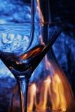 Vidrio y botella sobre backg azul Imagenes de archivo