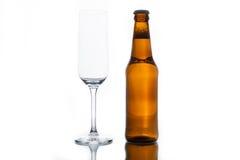 Vidrio y botella vacíos con la cerveza Imagen de archivo