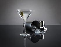 Vidrio y coctelera de Martini en fondo gris Foto de archivo