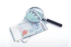 Vidrio y dinero de la lupa en el fondo blanco Pluma, lentes y gráficos Foto de archivo