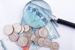 Vidrio y dinero de la lupa en el fondo blanco Pluma, lentes y gráficos Imagenes de archivo