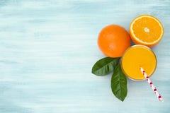 Vidrio y frutas del zumo de naranja en fondo tropical de madera azul imagen de archivo libre de regalías
