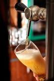 Vidrio y golpecito de relleno de cerveza Fotos de archivo libres de regalías