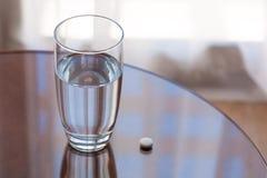 Vidrio y píldora de agua Foto de archivo