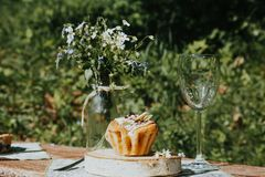 Vidrio y torta en una tabla soleada, un ramo de flores de la primavera para el humor fotos de archivo libres de regalías