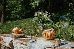 Vidrio y torta en una tabla soleada, un ramo de flores de la primavera para el humor imágenes de archivo libres de regalías