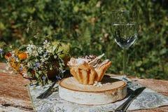 Vidrio y torta en una tabla soleada, un ramo de flores de la primavera para el humor foto de archivo libre de regalías