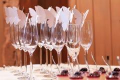 Vidrios adornados con las mariposas de papel en la tabla de una ceremonia Foto de archivo libre de regalías