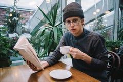 Vidrios agradables y sombrero del inconformista del individuo que leen un libro y que beben té en restaurante Imagen de archivo