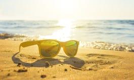 Vidrios amarillos el arena de mar, gafas de sol con paisaje hermoso del mar las gafas de sol se reflejan en la arena mojada de or Fotografía de archivo libre de regalías