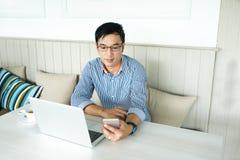 Vidrios asiáticos jovenes del ojo del control de la mano del hombre que miran fuera de la ventana, Cas imagenes de archivo