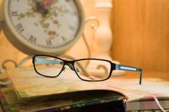 Vidrios azules clásicos que mienten en un libro de tapa dura abierto con un foco selectivo con un reloj borroso en el fondo Imágenes de archivo libres de regalías