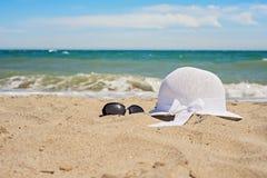 Vidrios blancos de mimbre del sombrero y de sol en la playa Imagen de archivo libre de regalías