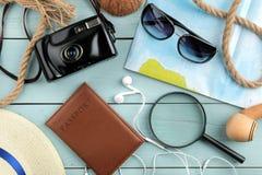 Vidrios, cámara, pasaporte, mapa y cáscaras del concepto del viaje en una tabla de madera azul Relajación holidays Visión superio imagen de archivo libre de regalías