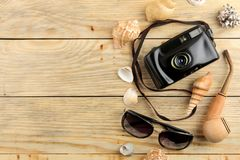 Vidrios, cámara y cáscaras del concepto del viaje en una tabla de madera natural Relajación holidays Visión desde arriba Espacio  fotografía de archivo libre de regalías