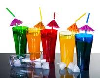 Vidrios coloreados con los cócteles y los cubos de hielo Imagen de archivo