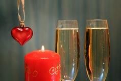 Vidrios con champán con el corazón y la vela Imagen de archivo libre de regalías