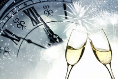 Vidrios con champán contra los fuegos artificiales y el reloj Fotos de archivo libres de regalías