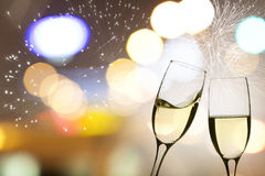 Vidrios con champán contra los fuegos artificiales y el reloj Imagen de archivo libre de regalías