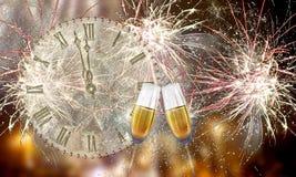 Vidrios con champán contra los fuegos artificiales y las horas Fotografía de archivo
