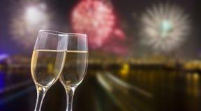 Vidrios con champán contra los fuegos artificiales y las luces de la ciudad Foto de archivo libre de regalías