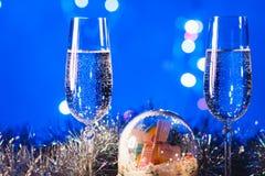 Vidrios con champán contra los fuegos artificiales y las luces del día de fiesta - Ce Imagenes de archivo
